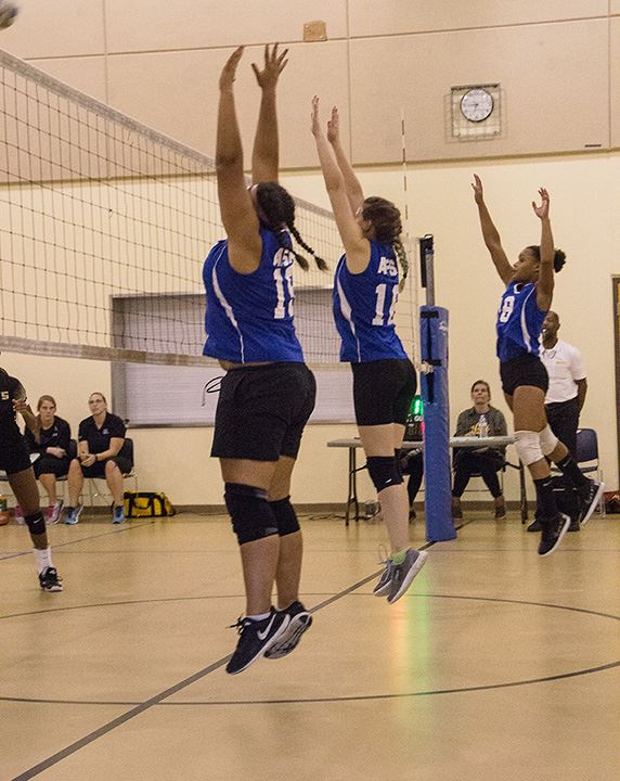 Three AFSA volleyball players jumping up to net at the same time.